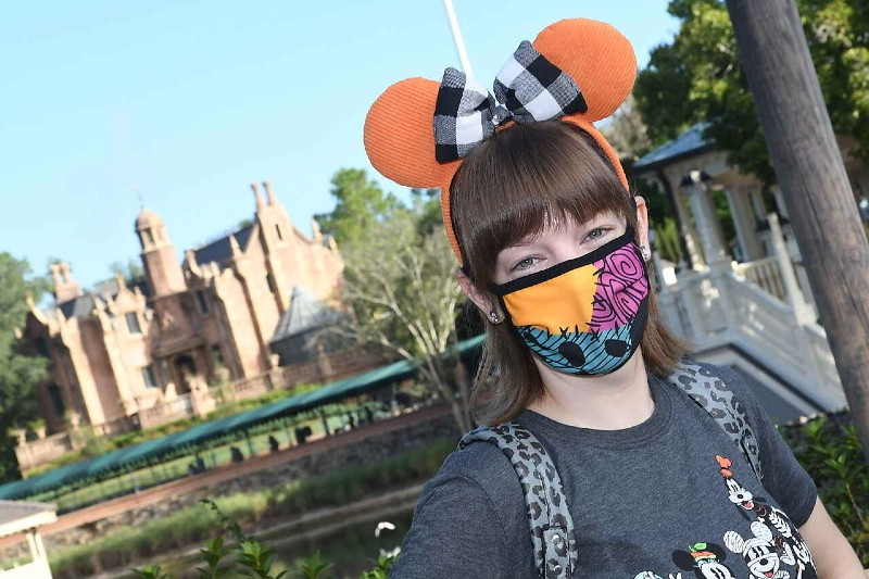woman wearing mask in front of haunted mansion at magic kingdom