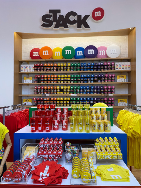 Mugs, cups, and other M&M themed merchandise available in all sorts of colors at the M&M store