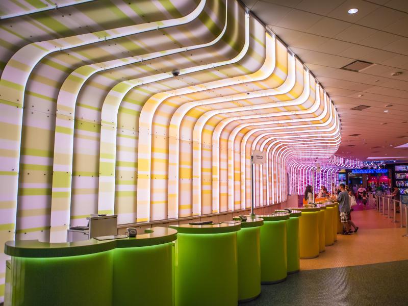 Green tables line an illuminated wall at Disney's Art of Animation Resort