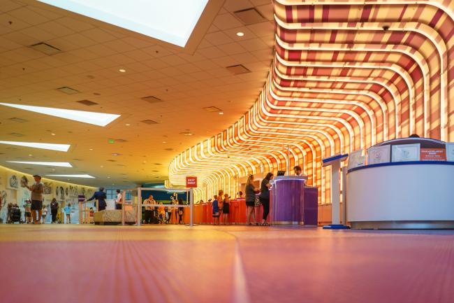 An illuminated wall shines behind the host desk at Disney's Arts of Animation Resort