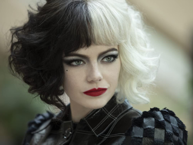 Emma Stone as Cruella De Vil is looking off into the distance and slightly smiling