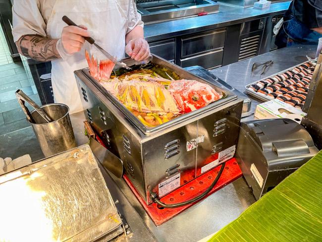 A Morimoto Asia chef prepares steamed snapper for the Suntory Morimoto Luau