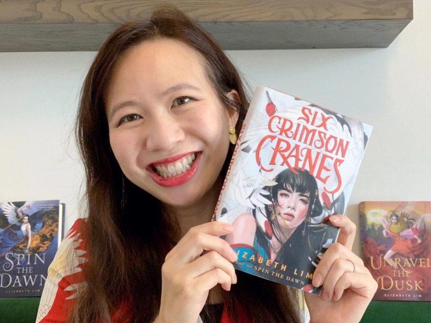 Author Elizabeth Lim holding up a copy of her book, Six Crimson Cranes