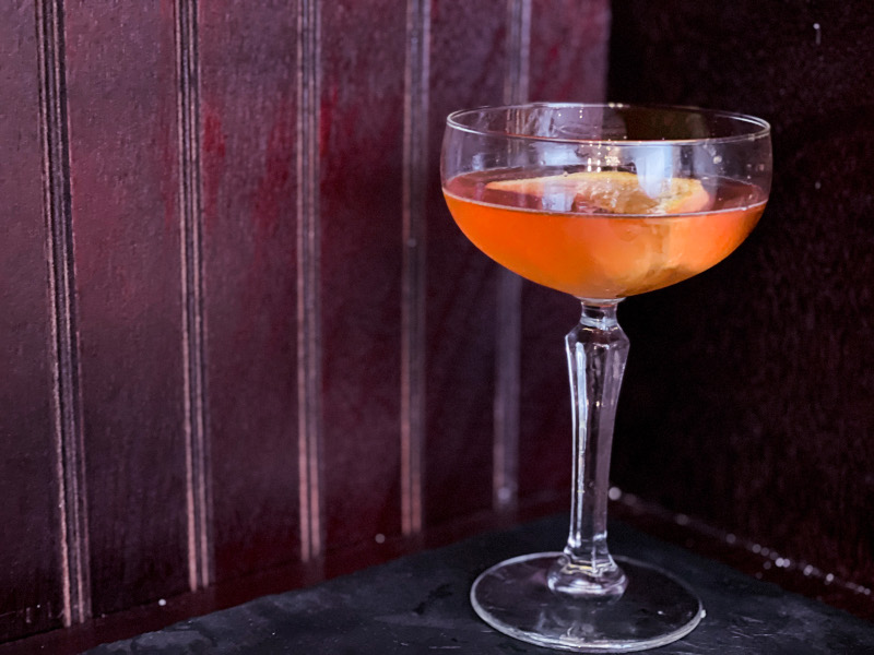 A dark orange-colored drink is displayed in a champagne coupe on a black display board, against a cherry wood wall.
