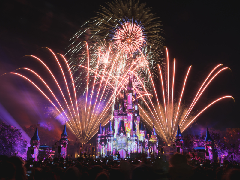 Fireworks flash around Cinderella Castle during a nightly showing of Happily Ever After