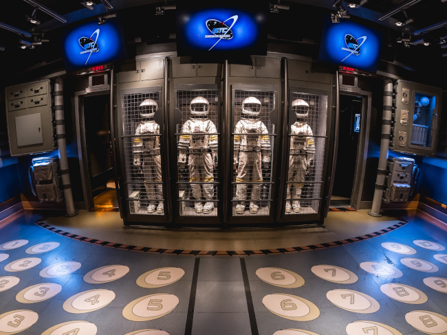 Space suits locked away in the line cue for Mission: SPACE
