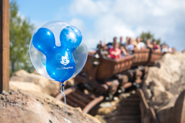 A mickey balloon waves in front of the Seven Dwarfs Mine Train