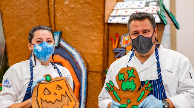 Pastry Sous Chef Gracie Gomez and Disneyland Resort President Ken Potrock working on 2021 haunted mansion gingerbread house