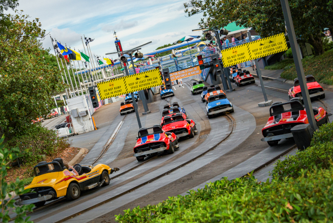 Cars zoom by on the Tomorrowland Speedway at the Magic Kingdom