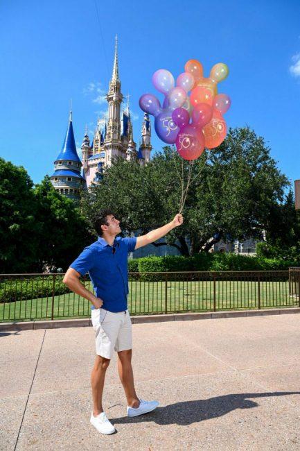 man-using-earidescent-ballons-magic-shop-photo-pass-cinderella-castle-wdw-50th-anniversary_disney